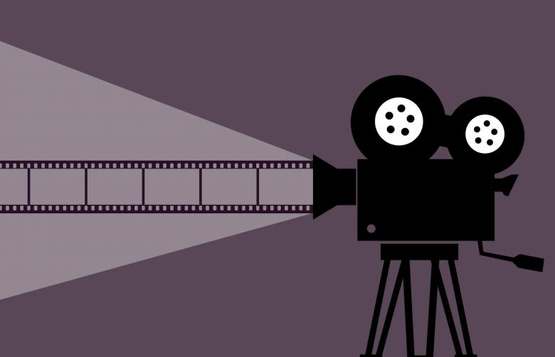 This is a picture of a movie projector against a gray background. The projector is projecting a film roll from its lens.